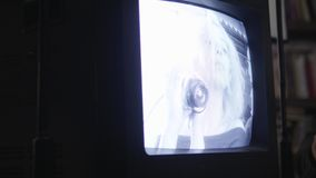La muchacha rubia que sostiene la cámara de seguridad aparece en la exhibición de la TV vieja, monocromática metrajes