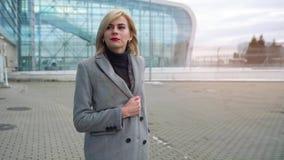 La muchacha rubia rueda una maleta cerca del terminal de aeropuerto Cámara lenta almacen de metraje de vídeo
