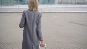 La muchacha rubia rueda una maleta cerca del terminal de aeropuerto - visión desde la parte posterior almacen de metraje de vídeo