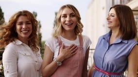 La muchacha rubia se está colocando en el centro con el entusiasmo y sus novias la besan en las mejillas Partido de gallina styli almacen de metraje de vídeo