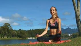 La muchacha rubia se relaja en actitud de la yoga en la estera por el lago metrajes