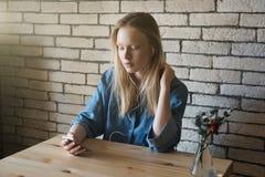 La muchacha rubia se sienta con los auriculares y mira en el teléfono que lo sostiene en una mano, la otra está enderezando el pe Foto de archivo