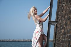 La muchacha rubia se vistió en una playa en la escalera fotos de archivo