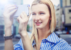 la muchacha Rubio-cabelluda, toma imágenes en el smartphone, sosteniéndolo Fotografía de archivo libre de regalías