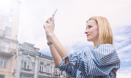 la muchacha Rubio-cabelluda, toma imágenes en el smartphone, sosteniéndolo Fotografía de archivo