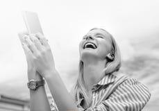 la muchacha Rubio-cabelluda, toma imágenes en el smartphone, sosteniéndolo con ambas manos, día, al aire libre Imagen de archivo
