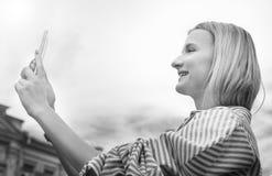 la muchacha Rubio-cabelluda, toma imágenes en el smartphone, sosteniéndolo con ambas manos, día, al aire libre Fotografía de archivo libre de regalías