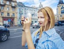 la muchacha Rubio-cabelluda, toma imágenes en el smartphone, sosteniéndolo con ambas manos, día, al aire libre Imagen de archivo libre de regalías