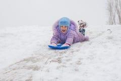 La muchacha rueda abajo en su estómago con de cabeza una nieve de la diapositiva Imagen de archivo