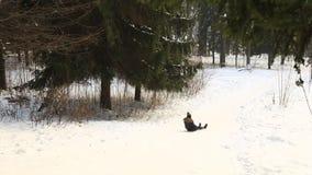 La muchacha rueda en una diapositiva de la nieve y en las caídas del final almacen de metraje de vídeo
