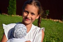 la muchacha rusa Diez-año-vieja sostiene una muñeca preferida imagenes de archivo
