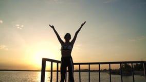 la muchacha 20s está haciendo ejercicios de respiración en el amanecer en la playa Mujer joven hermosa en yoga practicante de la  metrajes