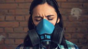 La muchacha saca la máscara de la contaminación atmosférica En fondo de la pared de ladrillo, máscara respiratoria metrajes