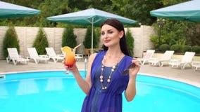 La muchacha saca sus gafas de sol que hacen una pausa la piscina metrajes