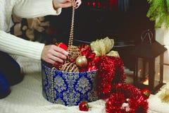 La muchacha saca una caja de decoraciones de la Navidad Imagenes de archivo