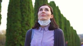 La muchacha saca una máscara médica de su cara e inhala profundamente el aire en el parque almacen de metraje de vídeo