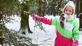 La muchacha sacude la nieve de la rama de árbol en la niñez feliz del bosque Diversión del invierno almacen de video