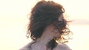 La muchacha sacude su pelo en la luz del sol almacen de metraje de vídeo