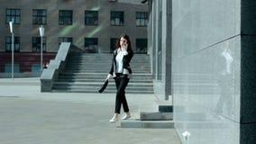 La muchacha sale de centro de negocios y de hablar en el teléfono almacen de video