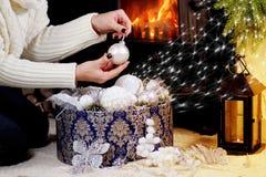 La muchacha sale decoraciones de la Navidad de la caja Imagenes de archivo