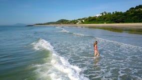 La muchacha sale del agua del océano a través de ondas espumosas almacen de video