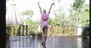 La muchacha sale a la terraza que estira vista posterior de los brazos detrás, mujer rubia disfruta de la opinión de la mañana de almacen de metraje de vídeo