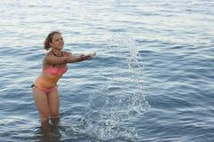 La muchacha salpica en la agua de mar Imagen de archivo libre de regalías