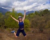La muchacha salta alegre en el camino de bosque del otoño fotografía de archivo libre de regalías