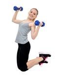 La muchacha salta con pesas de gimnasia Fotos de archivo