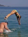 La muchacha salta en el mar Imagen de archivo