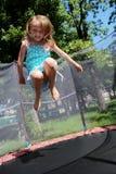 La muchacha salta en el trampolín Imagenes de archivo
