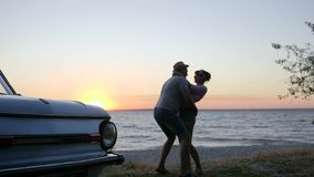 La muchacha salta en los hombres para apuntalar el río en ocaso, amantes felices de la puesta del sol en la orilla del mar, abraz metrajes