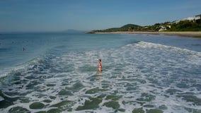 La muchacha salta en onda espumosa en el océano por el Palm Beach
