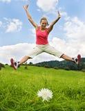 La muchacha salta en prado Imagen de archivo libre de regalías