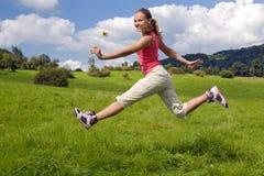 La muchacha salta en prado Imagen de archivo