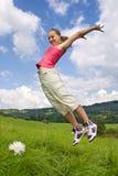 La muchacha salta en prado Fotos de archivo