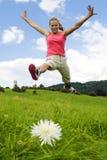 La muchacha salta en prado Fotografía de archivo