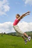 La muchacha salta en prado Fotos de archivo libres de regalías