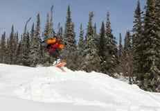 La muchacha salta en una snowboard en el bosque Fotografía de archivo libre de regalías