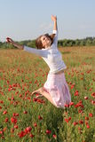 La muchacha salta sobre campo de la amapola Fotografía de archivo