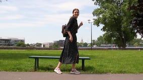 La muchacha sana hermosa feliz se mueve en danza y paseos en el parque al aire libre almacen de video