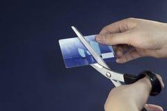 La muchacha scissors cortes una economía de la tarjeta de crédito foto de archivo