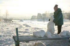 La muchacha sculpts un muñeco de nieve Fotos de archivo libres de regalías
