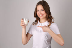 La muchacha señala su finger en el vidrio de leche Cierre para arriba Fondo blanco Imagen de archivo libre de regalías