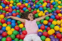 La muchacha se acuesta en una piscina plástica colorida de la bola Fotografía de archivo libre de regalías