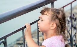 La muchacha se aflige en la cerca del metal Imágenes de archivo libres de regalías