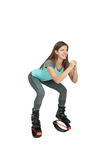 La muchacha se agacha en saltos del kangoo de las botas Imagen de archivo libre de regalías