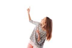 La muchacha se arrodilla abajo mientras que señala con los dedos índices a la copia s Fotografía de archivo libre de regalías