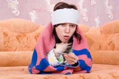 La muchacha se caía enferma y en el sofá Foto de archivo