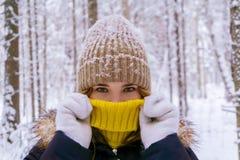 La muchacha se calentó respirando en el bosque del invierno imágenes de archivo libres de regalías